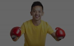 Teen boy posing in red boxing gloves
